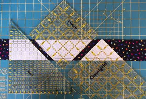 Tape paper templates to the underside of a ruler and cut along edges of ruler to cut the pieces.